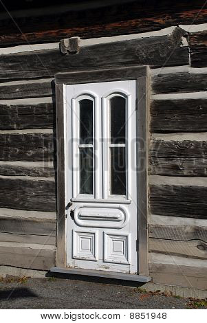 white door on old wood log house