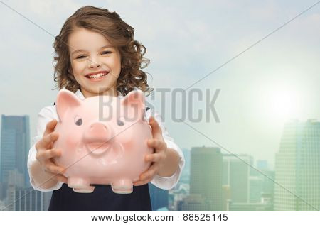 people, money, finances and savings concept - happy girl holding piggy bank over city background