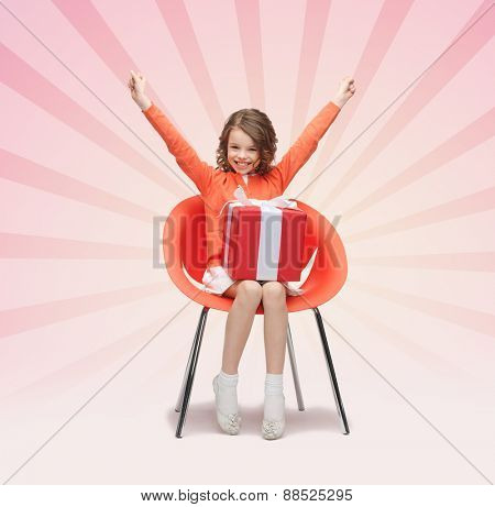people, christmas, holidays, presents and childhood concept - happy little girl with gift boxes and raised arms sitting on chair over pink burst rays background