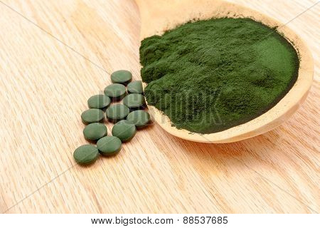 Closeup of an organic spirulina algae powder and pills in a wooden spoon poster