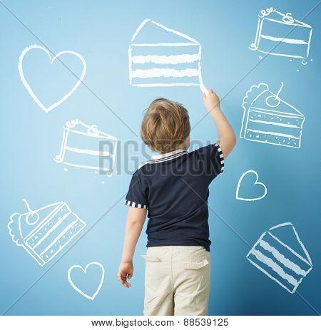 Little boy drawing cake symbols