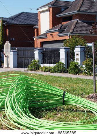 Fiber optic cable piled in front of residential housing
