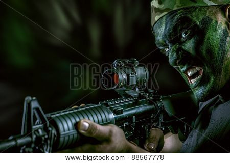 A soldier in war paint looks through the scope of automatic rifles. Military, war. Special forces. poster