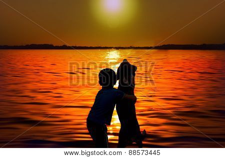Silhouette of boy and dog embracing at sunset