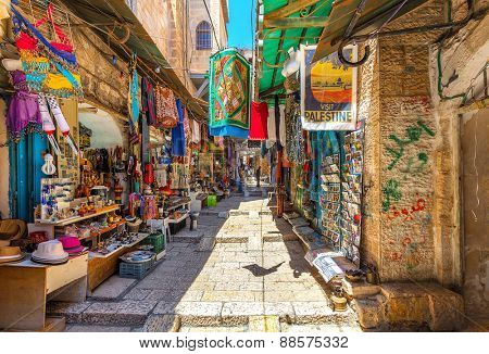 JERUSALEM, ISRAEL - JULY 10, 2014: Narrow stone street among stalls with traditional souvenirs and goods at bazaar in Old City - popular place among tourists and pilgrims visiting Jerusalem.