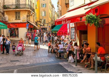 NICE, FRANCE - AUGUST 23, 2014: People in Old City of Nice - fifth most populous, second-largest French city on Mediterranean coast and one of the most visited with 4 million tourists every year.