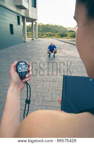 Trainer hand using chronometer to timing man training