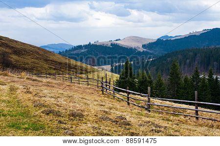 Fence near the meadow path on the hillside. Ukrainian Carpathians