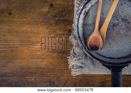 Wooden kitchen utensils on the table. Wooden spoon old pan in a retro style on wooden table. Free sp