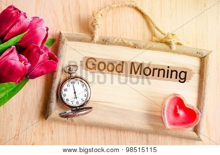 Good morning. Clock and red tulip with red candle heart shape on wooden background. poster