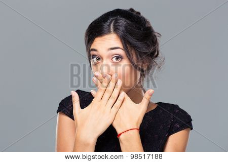 Portrait of a young woman covering her mouth on gray background and looking at camera