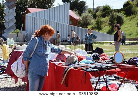 Woman Shopping Secondhand Hats And Caps At A Flea Market.