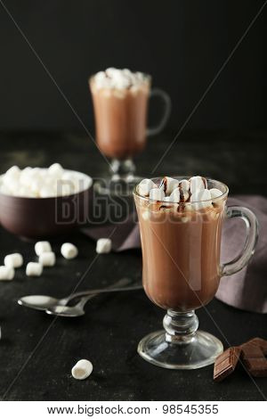 Glass of hot chocolate with marshmallows on black background