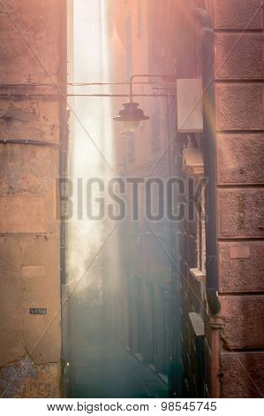 A narrow alley in Italy filled with smoke of a burning house lit by the sun rays poster