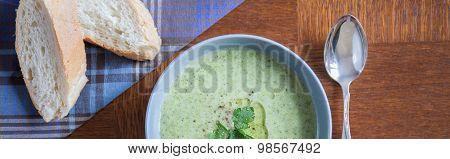 Tasty green soup served with a french baguette poster