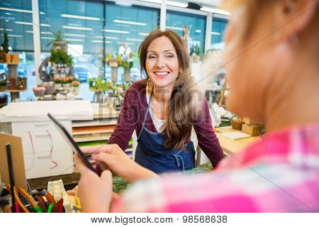 Happy florist looking at female customer using digital tablet in flower shop