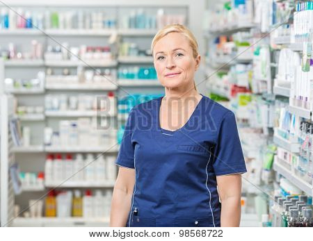 Portrait of confident female pharmacist in uniform standing at pharmacy