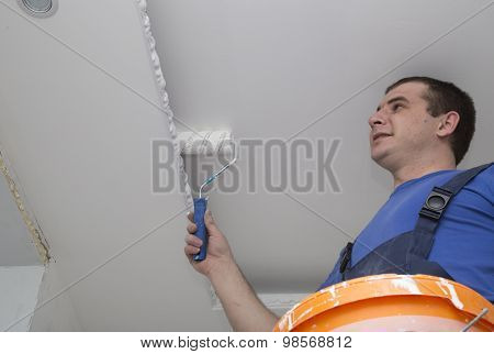 Man repairs the house inside with roller and bucket