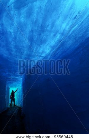Man silhouette in ice cave. Rhone glacier, Switzerland, Europe.