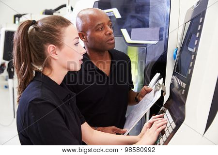 Female Apprentice Working With Engineer On CNC Machinery