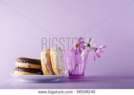 Delicious Colorful Donuts On Dish With Flowers In Glass