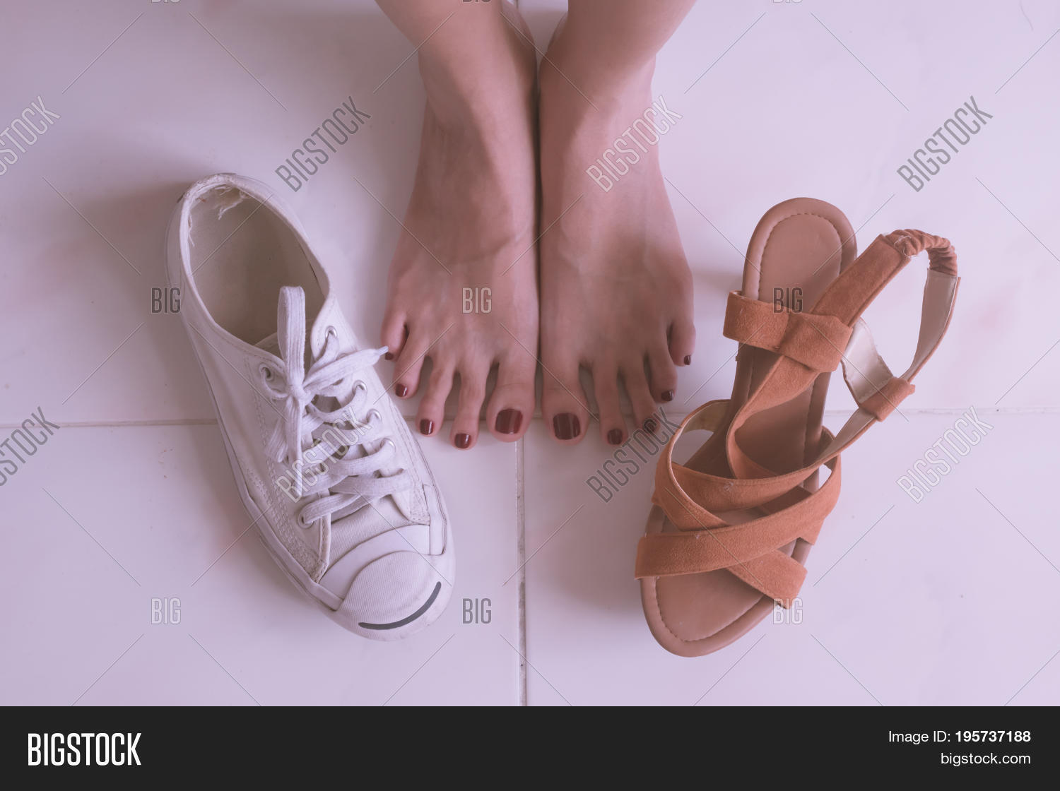 2529a05620db Close up of female feet with high heels shoes and casual sports shoes.