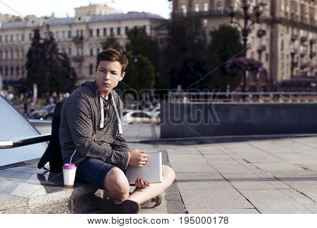 Serious young man with a tablet on the street of a big city