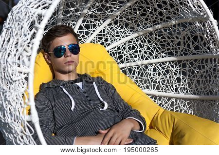 Handsome young man on a yellow pillow in a wicker chair close-up