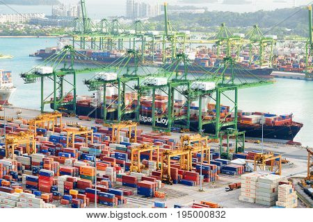 Singapore - February 17 2017: Amazing view of a container terminal at the Port of Singapore. Cargo ships docked in harbor. Ship-to-shore gantry cranes loading and unloading vessels at shipping yard.
