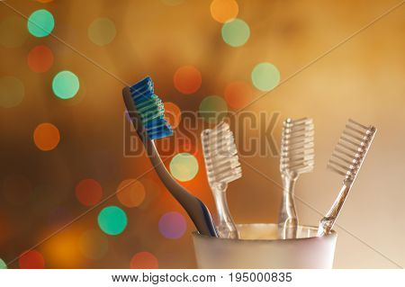 Set of tooth brushes in glass beaker.