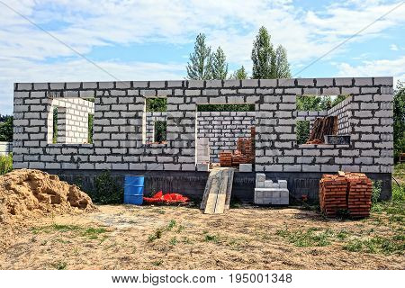 Construction of a white brick house in the yard against the sky