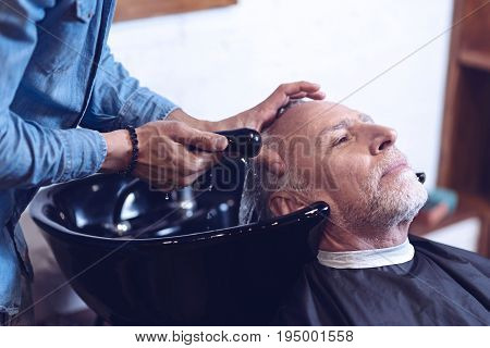 Washing hair. Nice good looking senior man sitting in the armchair and having his hair washed while visiting barbershop