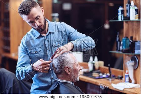 True professional. Serious handsome male hairdresser holding a comb and cutting his clients hair while being concentrated on his job