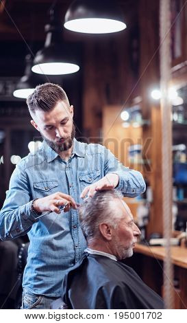 Professional stylist. Handsome good looking nice barber standing near his client and cutting his hair while doing his job