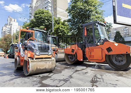 Among the summer noon five heavy road vibrating roller compactors and other equipment are ready for repair of the road in a modern city