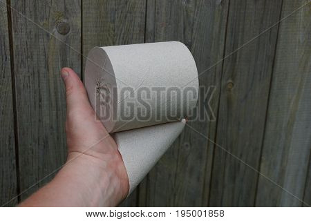A hand holds a roll of gray toilet paper against a wooden wall