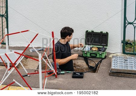 PARIS FRANCE - JUL 12 2017: Worker inside sewage manhole hole - telecomunication internet provider company working on implementation of fiber optic cables in sewage system using fiber optic welding machine