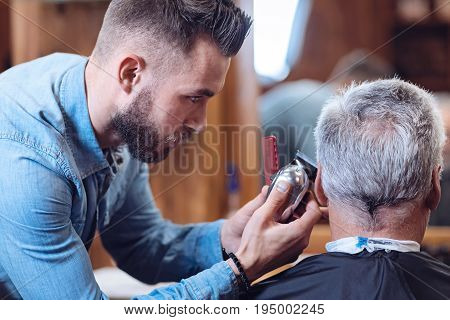 Perfect haircut. Professional nice male barber holding a hair cutting machine and concentrating on the job while working with a client