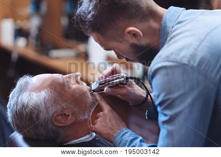 Professional tools. Handsome nice pleasant barber holding an electric shaver and using it while trimming his clients beard
