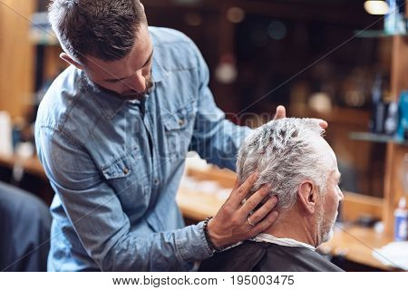 Trendy haircut. Serious professional male hairdresser looking at his clients hair and doing hair styling while working in the barbershop
