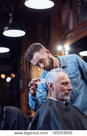 Ideal look. Handsome good looking bearded barded holding a comb and modeling his clients haircut while standing near him