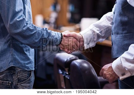Greeting gesture. Close up of a male handshake being done by nice pleasant men while greeting each other