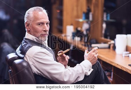 Unhealthy habit. Confident good looking senior man smoking a cigar and enjoying whisky while looking at you