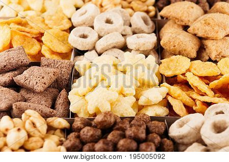 Corn flakes various shape and flavor - rings stars balls pads chocolate top view decorative pattern background.