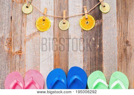 Pink blue and green flip flop sandals on wood background. Citrus fruits.
