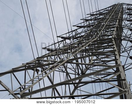 high voltage transmission line accent tower on cloudy sky background