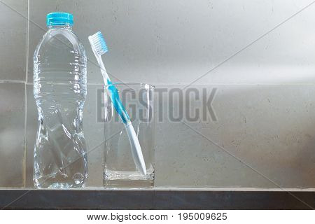 white toothbrush in clear glass cup and full bottle of drinking water in bathroom with bright morning light concept of clean and healthy dental room for copyspace