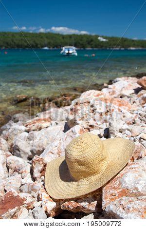 Straw hat on the stony beach of the Adriatic Sea - holiday on Croatia, Hvar island