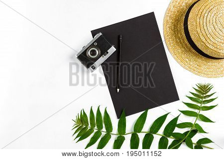 Straw hat with green leaves and old camera on white background, Summer background. Top view. Copy space. Still life. Flat lay