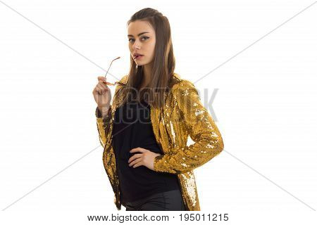 young chic girl worth gold jacket and holding a glasses isolated on white background
